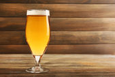 Glass of beer on wooden background — Stock Photo