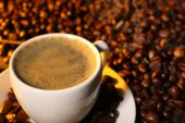 Cup of coffee with grains, closeup — Stock Photo