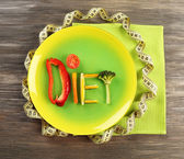 Word DIET made of sliced vegetables in plate with measuring tape on wooden table, top view — Stock Photo