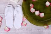 Spa bowl with water, rose petals, towel and slippers on light background. Concept of pedicure or natural spa treatment — Stock Photo