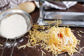 Making vermicelli with pasta machine on wooden background — Stock Photo