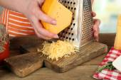 Closeup of female hands grating cheese — Stock Photo