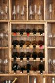 Shelving with wine bottles and glasses on wooden wall background — Stock Photo