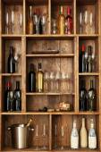 Shelving with wine bottles with glasses on wooden wall background — Stock Photo