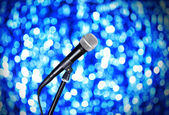 Microphone on stand on blue background — Stock Photo