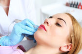 Cosmetologist applying permanent make up on lips — Stock Photo