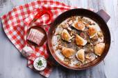 Fried dumplings with onion and bacon in frying pan, on wooden table background — Stock Photo