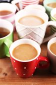 Cups of cappuccino on wooden table, closeup — Stock Photo