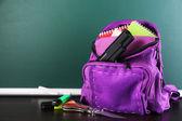 Gun in school backpack on wooden desk, on blackboard background — Stock Photo