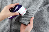 Female hands with Wool shaver on wool sweater background — Stock Photo
