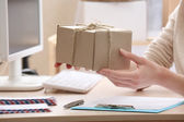 Woman gives parcel in post office — Stock Photo
