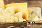 Different sort of cheese on wooden cutting board, closeup — Stock Photo
