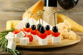 Cheese canapes with wine on table close up — Stockfoto