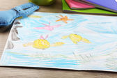 Kids drawing on white sheet of paper on wooden table, closeup — Stock Photo