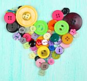Sewing buttons heart on wooden background — Stockfoto