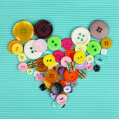 Sewing buttons heart on cloth background — Stockfoto