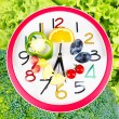 Food clock with vegetables and fruits as background. Healthy food concept — Stock Photo #71537843