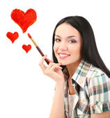 Beautiful young woman as painter with brush and red hearts isolated on white — Stock Photo