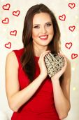 Smiling girl holding wicker heart on festive background — Stockfoto