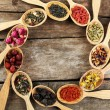 Collection of tea and natural additives in wooden spoons, on old wooden table — Stock Photo #71543463