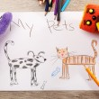 Kids drawing on white sheet of paper with toys on wooden table, closeup — Stock Photo #71546367