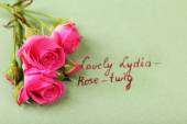 Beautiful rosy twig with inscription on paper background — Stock Photo