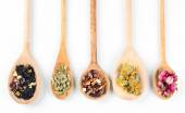 Collection of tea and natural additives in wooden spoons, isolated on white  — Stock Photo
