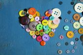 Sewing buttons heart on wooden background — Stock Photo