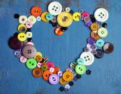 Sewing buttons heart on wooden background — Стоковое фото