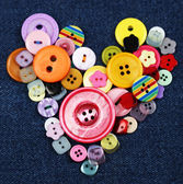 Sewing buttons heart on cloth background — Стоковое фото