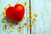 Red heart and cod liver oil on blue wooden background — Stock Photo