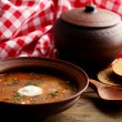 Ukrainian beetroot soup - borscht in bowl and pot, on napkin, on wooden background — Stock Photo #71558683