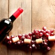 Glass bottle of wine with corks and grapes on wooden table background — Stock Photo #71559029