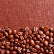 Frame of coffee beans on color sackcloth background — Stock Photo #71559273