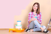 Beautiful girl lying on floor with equipment for painting wall — Stock Photo