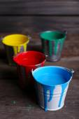 Metal buckets with colorful paint on wooden background — Stock Photo