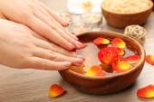 Female hands and bowl of spa water with flowers, closeup — Stock Photo