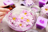 Female hand with bottle of essence and bowl of aroma spa water on wooden table, closeup — Stock Photo