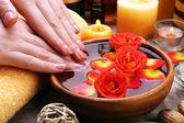 Vrouwelijke handen met kom aroma spa water op houten tafel, close-up — Stockfoto