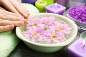 Female hands with bowl of aroma spa water on wooden table, closeup — Stock Photo