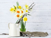 Fresh narcissus flowers with willow sprigs on wooden background — Stock Photo