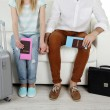 Legs of young happy couple with baggage and tickets, sitting on sofa — Stock Photo #71795439