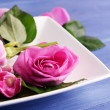 Beautiful pink roses in white plate on wooden table, closeup — Stock Photo #71794925