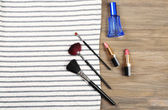 Striped T-shirt and various cosmetics on wooden background — Stock Photo