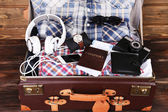 Packed suitcase of vacation items on wooden background — ストック写真