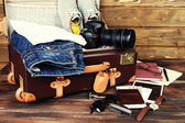 Packed suitcase of vacation items on wooden background — Stock Photo