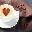 Cup of cappuccino with heart of cocoa on wooden table — Stock Photo #71815771