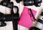 Modern cameras with glasses and pink diary on wooden table, top view — Stock Photo