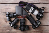 Still life with modern cameras on wooden table, top view — Stock Photo