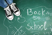 Female feet on blackboard background with inscriptions and sketches — Stock Photo